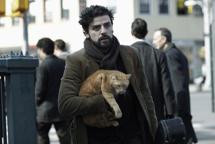 Photo d'Oscar Isaac dans le film Inside Llewyn Davis des frères Coen. L'acteur marche dans la rue, porte un chat et un étui de guitare et semble agacé.