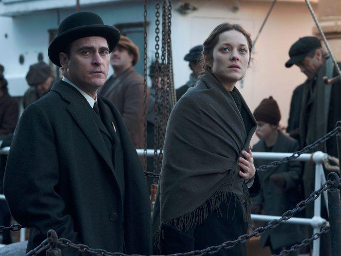 Photo de Joaquin Phoenix et Marion Cotillard dans le film The Immigrant de James Gray. Le couple marche sur un bateau et observent tristement le paysage sur leur droite.