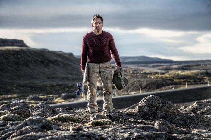 Photo de Ben Stiller dans son film La vie de Walter Mitty. L'acteur est dans dans un paysage montagneux d'Islande et tient un long board et un sac à dos.