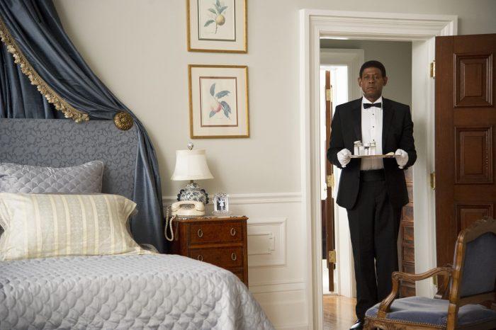 Photo de Forrest Whitaker dans le film Le Majordome de Lee Daniels. Le majordome attend en tenant un plateau à l'entrée d'une chambre.