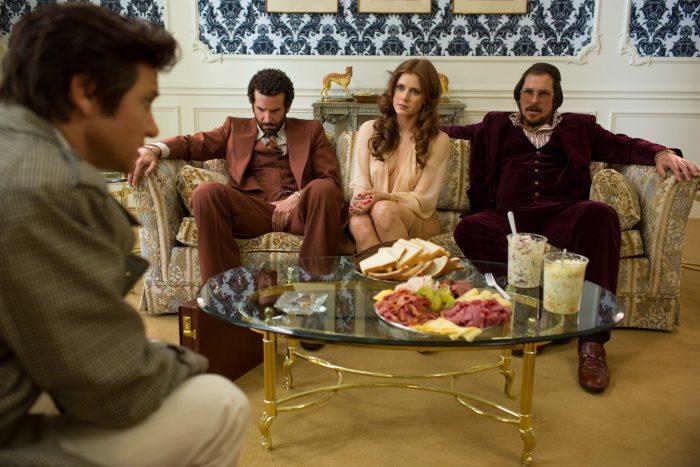 Photo de Jeremy Renner, Bradley Cooper, Amy Adams et Christian Bale dans le film American Bluff. Les trois derniers comédiens sont assis dans un luxueux canapé face à Renner. Un buffet est servi sur une table entre eux.
