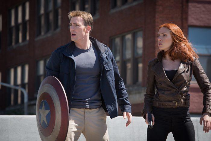 Photo de Chris Evans et Scarlett Johansson dans le film Captain America : Le Soldat de L'Hiver. En tenue de civils, Captain America et Black Widow semblent faire face à une menace et sont en alerte.