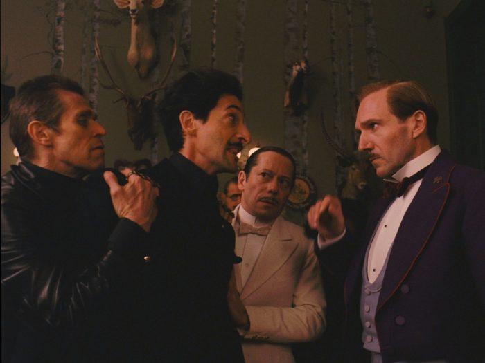 Photo de Willem Dafoe, Adrien Brody, Mathieu Amalric et Ralph Fiennes dans le film The Grand Budapest Hotel de Wes Anderson. Brody s'apprête à bondir sur Fiennes mais est retenu par les deux autres comédiens.