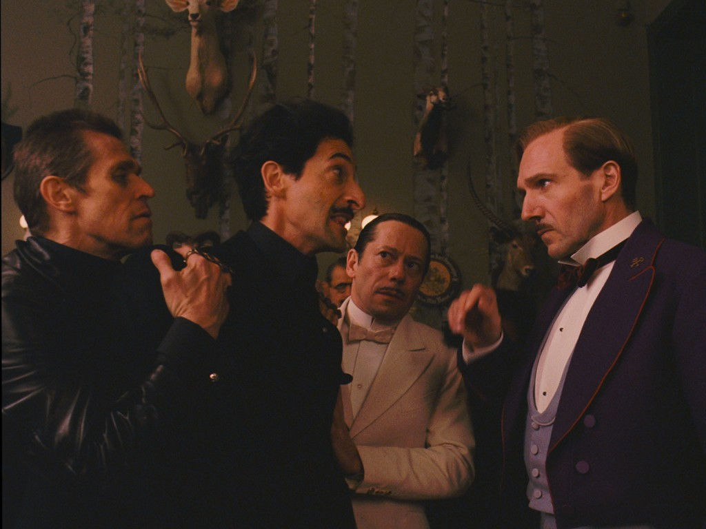Photo de Willem Dafoe, Adrien Brody, Mathieu Amalric et Ralph Fiennes dans le film The Grand Budapest Hotel de Wes Anderson. Brody s'apprête à bondir sur Fiennes mais est retenu par les deux autres comédiens.