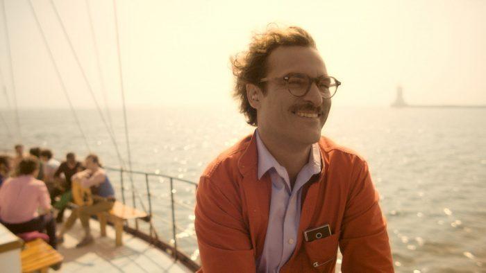 Photo de Joaquin Phoenix dans Her. L'acteur est sur un bateau, seul, et semble euphorique malgré le fait qu'il soit à l'écart d'autres personnes.