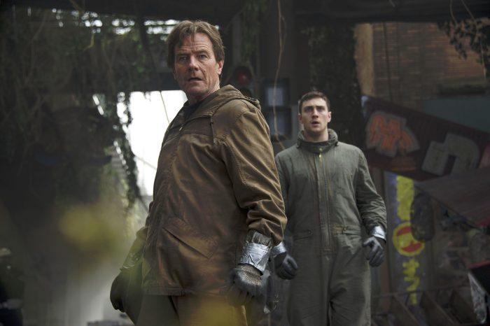 Photo de Bryan Cranston et Aaron Taylor Johnson dans le film Godzilla de Gareth Edwards. Les deux observent quelque chose dans une zone désaffectée et semblent stupéfaits.