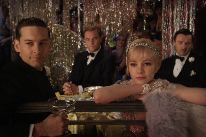Photo de Tobey Maguire, Leonardo DiCaprio, Carey Mulligan et Joel Edgerton dans le film Gatsby Le Magnifique. les acteurs contemplent un spectacle lors d'une luxueuse fête.