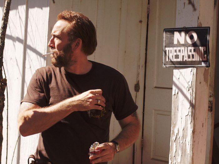 Photo de Nicolas Cage dans Joe. L'acteur prend une cigarette dans son paquet tout en se retournant.