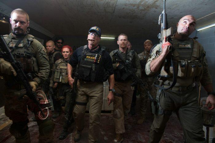 Photo du film Sabotage de David Ayer. L'équipe de la DEA menée par Schwarzenegger avance armée dans un sous-sol.