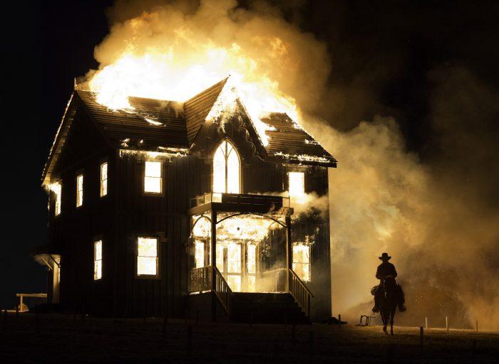 Photo de Tommy Lee Jones dans le film The Homesman. L'acteur est à cheval, dans la nuit, avance vers l'objectif à côté d'une maison en feu.