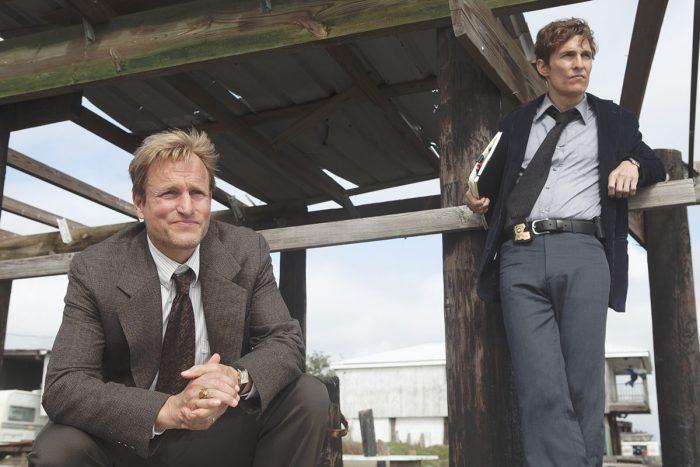 Photo de Woody Harrelson et Matthew McConaughey dans la première saison de True Detective. Les deux policiers sont en costume. L'un est accroupi, l'autre adossé à une rambarde. Ils semblent observer une scène de crime.