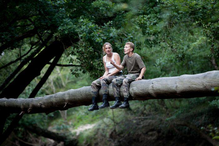 Photo d'Adèle Haenel et Kevin Azais dans le film Les combattants. Les deux acteurs sont en tenue militaire dans la forêt et discutent assis sur un arbre.