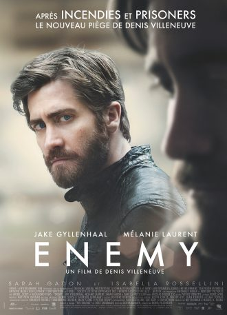 Affiche du film Enemy de Denis Villeneuve. Jake Gyllenhaal y contemple son double avec un regard agressif à travers une vitrine.