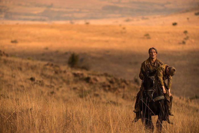 Photo de Mads Mikkelsen dans le film The Salvation. L'acteur est à cheval dans un vaste paysage désert et porte un enfant mort.