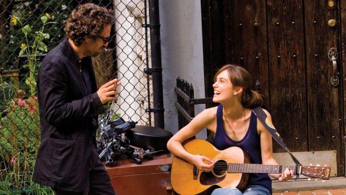 Photo de Mark Ruffalo et Keira Knightley dans le film New York Melody. Sur le palier d'une maison, l'actrice joue de la guitare et semble rire d'une blague de Ruffalo.