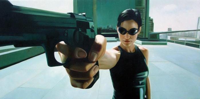 Photo de Carrie Anne Moss dans Matrix. Sur le toit d'un immeuble, Trinity pointe son arme à gauche de l'objectif.
