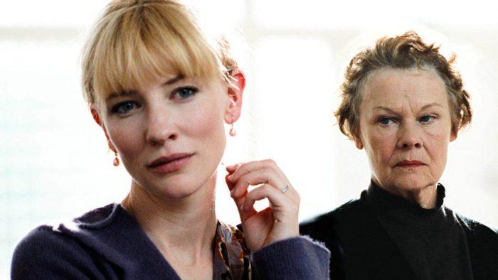 Photo de Cate Blanchett et Judi Dench dans le film Chroniques d'un scandale. Blanchett est pensive alors que Dench la contemple avec un regard sombre.