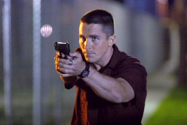 Photo de Christian Bale dans le film Bad Times de David Ayer. L'acteur pointe son arme sur un personnage que l'on ne voit pas.