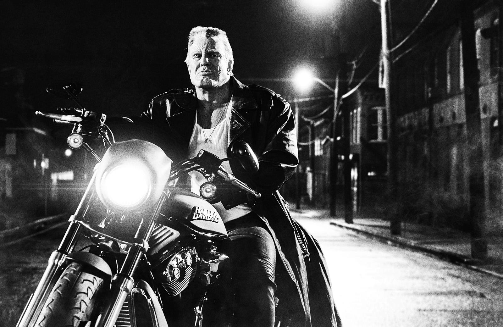 Photo de Marv dans le film Sin City : J'ai Tué Pour Elle. Le héros est sur sa moto, face à l'objectif.