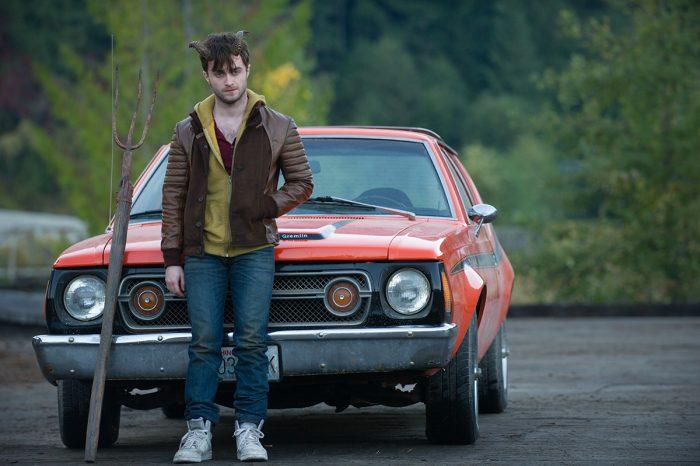 Photo de Daniel Radcliffe dans le film Horns d'Alexandre Aja. L'acteur arborant des cornes se tient devant une voiture avec une fourche.