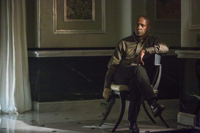 Photo de Denzel Washington dans le film The Equalizer d'Antoine Fuqua. L'acteur est assis sur un fauteuil dans une villa, une arme à la main.