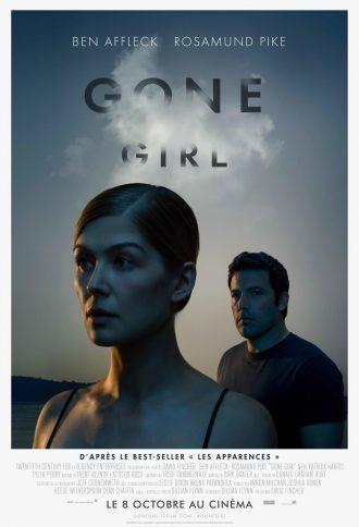 Affiche de Gone Girl de David Fincher. Dans la pénombre d'un soleil couchant, Rosamund Pike se tient au premier plan tandis que son mari incarné par Ben Affleck l'observe étrangement.
