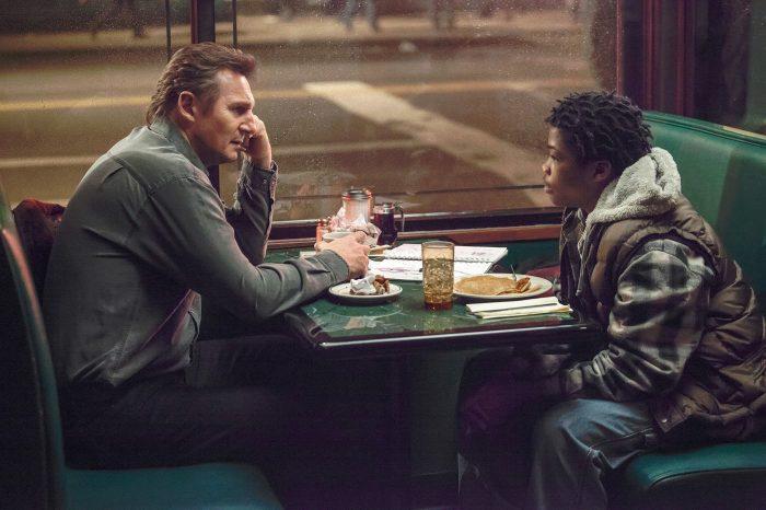 Photo de Liam Neeson dans le film Balade entre les tombes. L'acteur est assis à la table d'un diner et discute avec un jeune ami à lui.