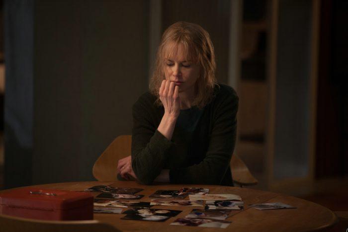 Photo de Nicole Kidman dans le film Avant d'aller dormir. L'actrice est assise à une table et contemple une série de photos.