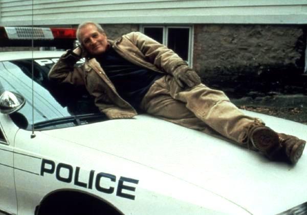 Photo de Paul Newman dans le film Un homme presque parfait. L'acteur est couché sur une voiture de police et regarde l'objectif en souriant.