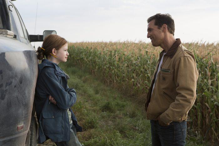 Photo de Mackenzie Foy et Matthew McConaughey dans le film Interstellar de Christopher Nolan. Le père et sa fille discutent près de leur voiture dans un champ.