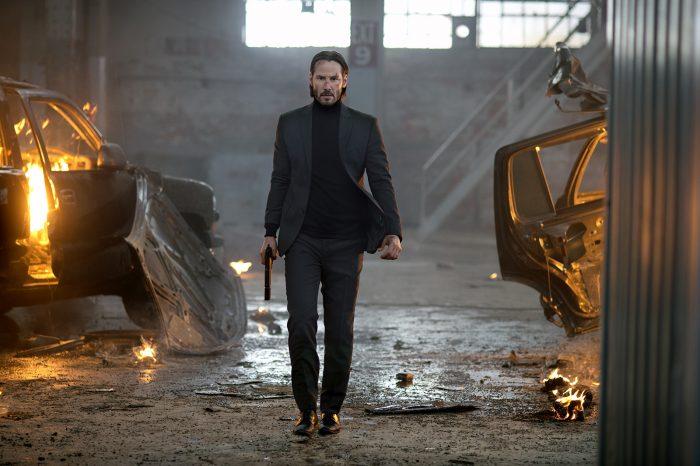 Photo de Keanu Reeves dans le film John Wick. L'acteur avance armé face à l'objectif dans un entrepôt très endommagé.