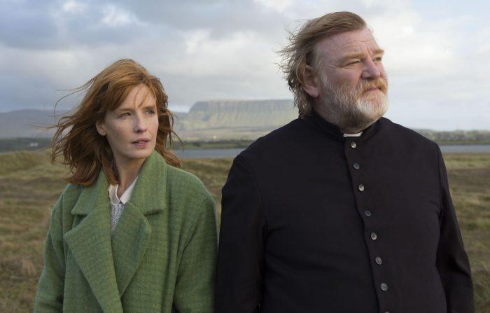 Photo de Kelly Reilly et Brendan Gleeson dans le film Calvary. Le prêtre et sa fille marchent ensemble dans un paysage verdoyant d'Irlande.
