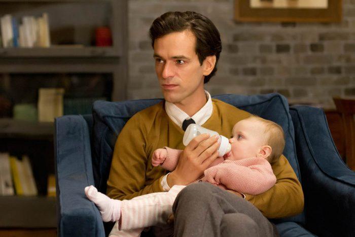 Photo de Romain Duris dans le film Une nouvelle amie. L'acteur est assis dans un fauteuil et nourrit un bébé. Il semble écouter un autre personnage.