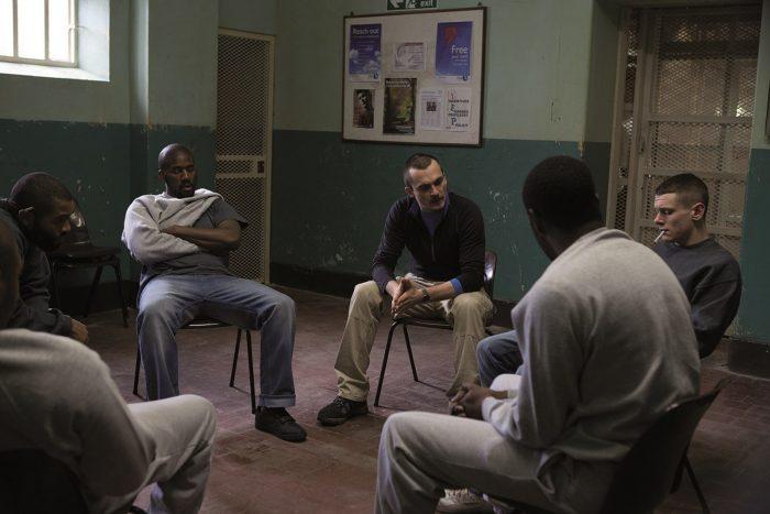 Photo tirée du film Les poings contre les murs. Nous y voyons plusieurs prisonniers discuter avec un éducateur en cercle dans une salle commune de la prison.