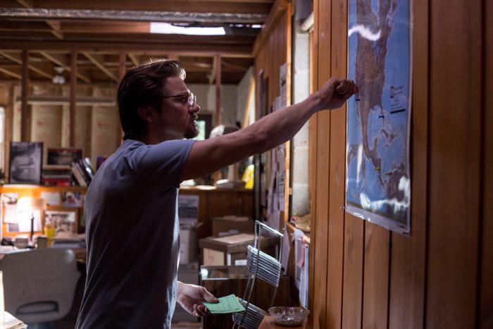 Photo de Jeremy Renner dans le film Secret d'Etat. L'acteur est pris de profil en train d'observer et de marquer une carte.