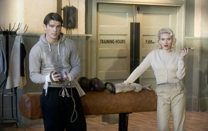 Photo de Josh Hartnett et Scarlett Johansson dans Le Dahlia Noir de Brian De Palma. Le premier sort d'un entrainement de boxe alors que la seconde fume une cigarette. Ils semblent regarder un troisième personnage.