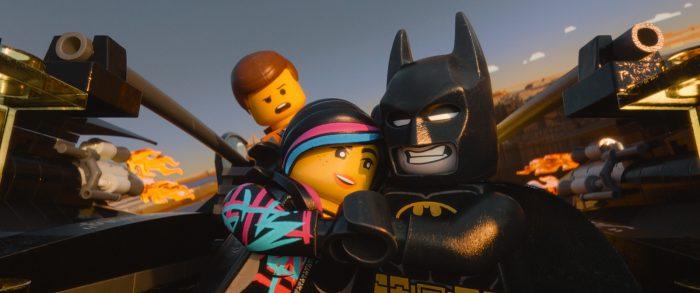 Photo du film La grande aventure Lego, sur laquelle nous voyons l'héroïne et Batman s'étreindre. Le héros est derrière et paraît très jaloux.
