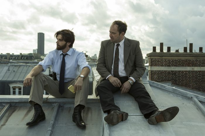 Photo de Raphael Personnaz et Olivier Gourmet dans le film L'affaire SK1. Les deux acteurs sont assis et discutent sur un toit de Paris.