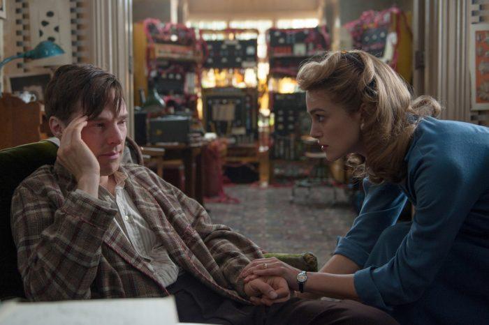 Photo de Benedic Cumberbatch et Keira Knightley dans le film The Imitation Game. Le premier est assis sur un fauteuil, semble malade alors qu'elle pose une main sur lui tendrement et semble vouloir l'aider.