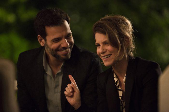 Photo de Laurent Lafitte et Marina Foïs dans le film Papa ou Maman. Les deux comédiens discutent et rient ensemble face à d'autres personnes.