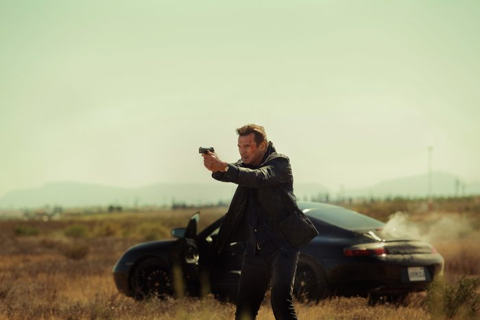 Photo de Liam Neeson dans le film Taken 3. L'acteur vient de sortir d'une Porsche dans un paysage désert et braque son arme sur un ennemi.