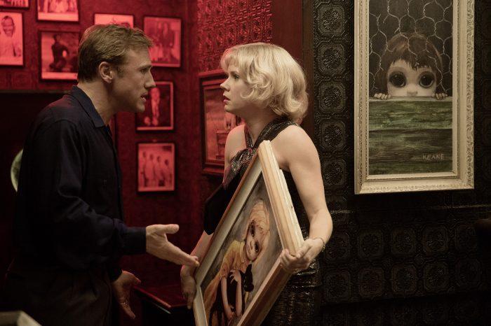 Photo de Christoph Waltz et Amy Adams dans le film Big Eyes de Tim Burton. Adams porte l'un de ses tableaux avec un air effrayé et Waltz tente de la raisonner en la manipulant.