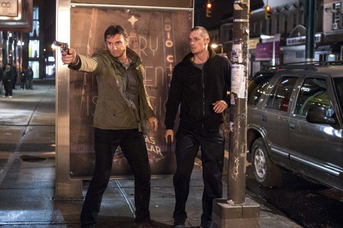 Photo de Liam Neeson et Joel Kinnaman dans le film Night Run. Neeson braque son arme sur un ennemi commun dans une rue de New York.