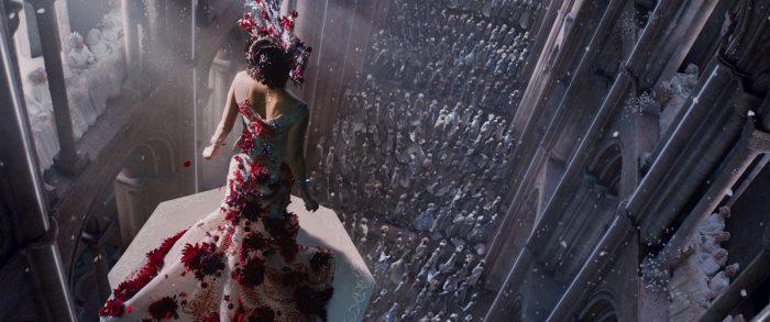 Photo de Mila Kunis dans le film Jupiter Ascending des Wachowski. L'actrice est prise de haut et de dos, en tenue de reine face à ses sujets dans une énorme chapelle.