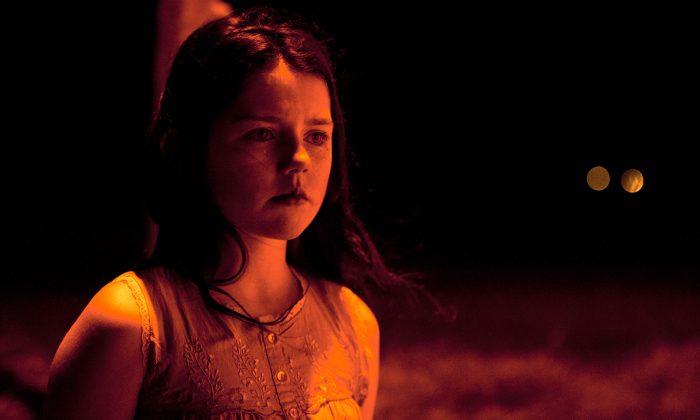 Photo de Missy Keating dans le film Dark Touch. La jeune fille se tient debout seule dans la nuit, éclairée par une lumière rouge.