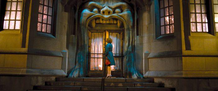 Photo de Christina Hendricks dans le film Lost River de Ryan Gosling. La comédienne entre dans un étrange immeuble, où les portes s'apparentent à la bouche d'une créature prête à engloutir sa victime.