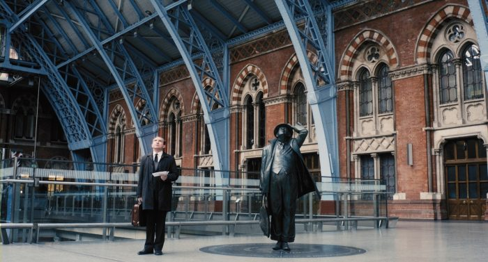 Photo d'Eddie Marsan dans le film Une belle fin. l'acteur semble perdu dans une gare et effectue une pose similaire à celle de la statue placée à sa droite.