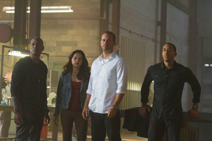Photo de Tyrese, Michelle Rodriguez, Paul Walker et Ludacris dans Fast & Furious 7 de James Wan. Les acteurs semblent écouter un autre protagoniste dans leur local de travail.