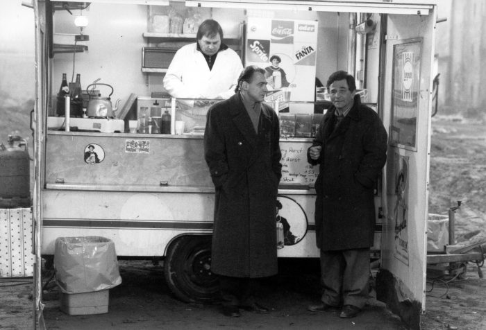 Photo de Bruno Ganz et Peter Falk dans le film Les ailes du désir de Wim Wenders. Les deux comédiens échangent à un stand de hot-dog à Berlin.