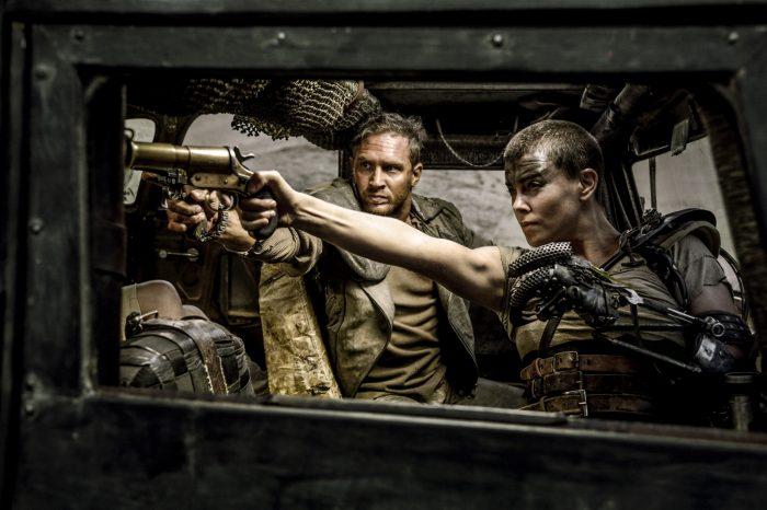 Photo de Tom Hardy et Charlize Theron dans le film Mad Max : Fury Road. A l'avant d'un véhicule, les deux personnages sont retournés et visent un ennemi commun.